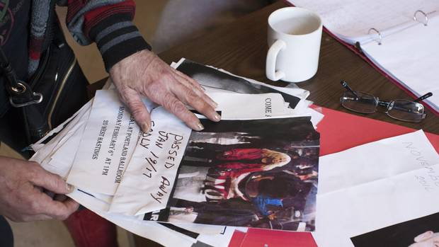 Lorna Bird, president of the Vancouver Area Network of Drug Users, looks through a folder with memorials of people who have died of overdoses.