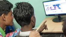 Kalim Khan, right, looks at his Facebook profile (with Saify Ali Khan) at the Star Cyber cafe in Lado Sarai near the Ummeed Aman Ghar home for boys in Mehrauli where he stays, in India, on Jan. 29, 2013. (SIMON DE TREY-WHITE FOR THE GLOBE AND MAIL)