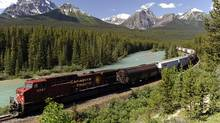 A Canadian Pacific Railway freight train runs along the Bow River and distant Rocky Mountains on the main line near Lake Louise, Alta. (LARRY MACDOUGAL/LARRY MaCDOUGAL/THE CANADIAN PRESS)