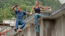 "Paul Walker and Mia Toretto leap into action in a scene from ""Fast Five."" (Jaimie Trueblood)"
