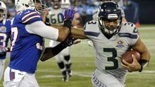 Seattle Seahawks quarterback Russell Wilson, right runs the ball against the Buffalo Bills during their NFL game in Toronto, December 16, 2012. (J.P. Moczulski/The Globe and Mail)