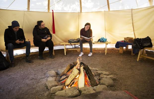 First Nations Trent University students sit in a campus tepee in Peterborough, Ont., on Nov. 28. As members of the school's native association, they hold their weekly meetings around a fire in the structure.