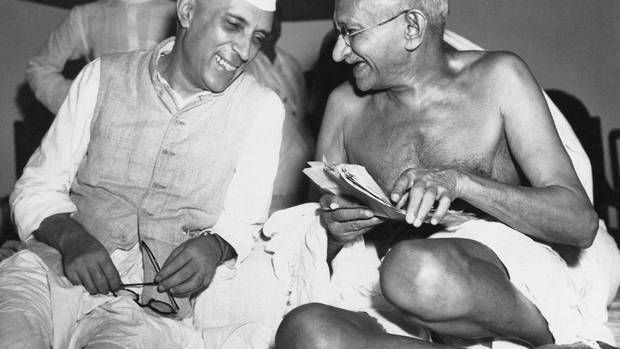 Mohandas Gandhi, right, who led India to its independence, laughs with the nation's first post-independence prime minister, Jawaharlal Nehru, at the All-India Congress committee meeting on July 6, 1946. (MAX DESFOR/AP)