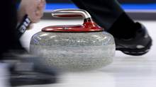A slow camera shutter speed blurrs a curling stone as curls down the ice (JONATHAN HAYWARD/THE CANADIAN PRESS)