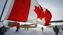 A Canadian flag flies from a snowmobile as military personnel gather during a sovereignty patrol in Eureka, Nunavut, on Mar. 31, 2007. (Jeff McIntosh/CP)