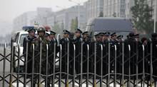 Policemen stand guard inside the north gate of Foxconn Tech-Industry Park in Taiyuan, Shanxi province, Sept. 25, 2012. A Chinese factory owned by iPhone assembler Foxconn resumed production on Tuesday after a riot involving 2,000 workers had forced it to close for 24 hours. (STAFF/REUTERS)