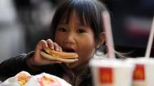 A child eats a hamburger outside a McDonald's fast food restaurant in downtown Milan Oct. 16, 2012. (STEFANO RELLANDINI/REUTERS)