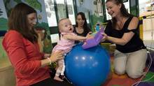 Aurora Blomerus, whos about to celebrate her first birthday, participates in the Beanstalk Program with, from left to right, occupational therapist Alaine Rogers, physiotherapist Stephanie So, and mom Nicole at the Hospital for Sick Children in Toronto on Monday. (Darren Calabrese/THE CANADIAN PRESS)