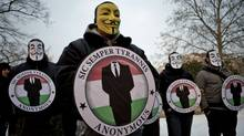 Protesters wearing Guy Fawkes masks and the logo of online hacker group Anonymous stage a rally in Budapest on Feb. 11, 2012. (Janos Marjai/AP)