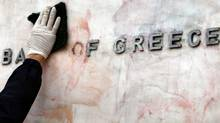 A worker cleans red and black paint off the sign of the Bank of Greece in Athens after weekend riots. (Thanassis Stavrakis/Thanassis Stavrakis/Associated Press)