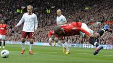 Manchester United's Ashley Young is fouled by Aston Villa's Ciaran Clark to win a penalty during their English Premier League soccer match at Old Trafford in Manchester, northern England April 15, 2012. (NIGEL RODDIS/Reuters)