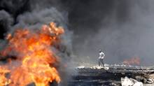 A masked Palestinian protester walks next to burning tyres during a weekly Friday protest against the Jewish settlement of Qadomem, near the West Bank City of Nablus April 25, 2014. (MOHAMAD TOROKMAN/REUTERS)