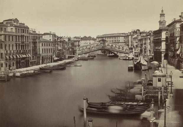 Gondolas along the sides of the Grand Canal in front of the Rialto Bridge, between 1890 and 1899.