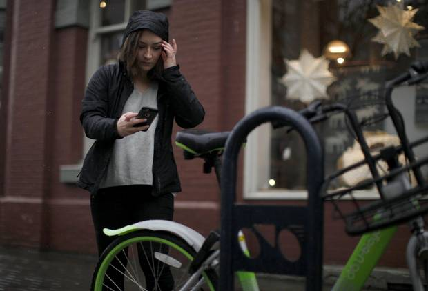 Carly Eldstrom uses the U-Bicycle app on her phone to scan a barcode to unlock a bicycle along Douglas St. in Victoria, B.C.