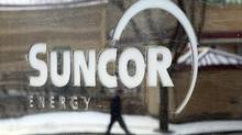 A pedestrian is reflected in a Suncor Energy sign in Calgary in this file photo. (Jeff McIntosh/The Canadian Press)