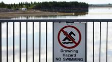 A no-swimming sign hangs on the banks of a lake near Innisfail, Alta., while a boom stretches out to contain a pipeline leak on June 12, 2012. (Jeff McIntosh/THE CANADIAN PRESS)