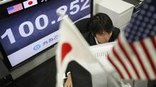 An employee of a foreign exchange trading company works in front of a monitor displaying the Japanese yen's exchange rate against the U.S. dollar in Tokyo Nov. 15, 2013. (Toru Hanai/Reuters)
