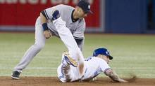 Toronto Blue Jays Brett Lawrie (right) is tagged by New York Yankees shortstop Derek Jeter as he tries to make it back to second base during the first inning of American league baseball action in Toronto on Friday September 28 , 2012. (Chris Young/THE CANADIAN PRESS)