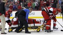 Joni Pitkanen, in stretcher, (25), of Finland, being taken off the ice on a stretcher with help from teammates Jiri Tlusty (19), far left, and and Tim Gleason (6), right, during the second period of an NHL game against the Washington Capitals in Raleigh, N.C. The Hurricanes say Pitkanen will miss the rest of the season with a broken heel. General manager Jim Rutherford disclosed the severity of Pitkanen's injury Wednesday, April 3, 2013. (CHRIS SEWARD/AP)
