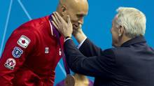 IOC delegate Richard Pound (right) touches the cheeks of Brent Hayden of Canada after presenting him with his bronze medal for his performance in the men's 100m freestyle at the Olympic Games in London on Wednesday August 1, 2012. (Frank Gunn/THE CANADIAN PRESS)