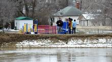 Onlookers watch the flood situation in Lumsden, Sask. in the Qu'Appelle Valley town northwest of Regina on Sunday April 17, 2011. The Towns of Lumsden and Craven are under a flood watch as water in the river has reached the tops of the protective dykes installed to protect them. (Roy Antal/The Canadian Press/Roy Antal/The Canadian Press)