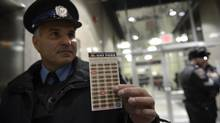Employees say just about every method of payment has been compromised, including the sort of day-pass displayed here by Transit enforcement officer Bill Perivolaris. (Fred Lum/The Globe and Mail)