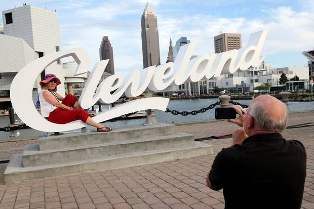 Donna Metz has her photo taken by husband Martin with the Cleveland skyline in the background on the sidelines of the Republican National Convention on July 17, 2016.