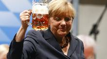 German Chancellor and top candidate for the Christian Democratic Union (CDU) Angela Merkel toasts with beer after her speech during an electoral rally in Dachau near Munich August 20, 2013. A new euro zone purchasing managers' survey showed surprising strength. (MICHAEL DALDER/REUTERS)