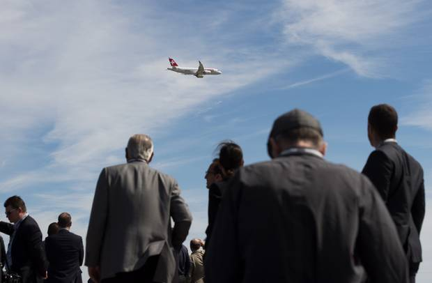 Guests line the tarmac to watch the fly-by of a Bombardier CS100 aircraft during a 2015 Toronto event.