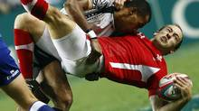 Wales' Lee Williams (bottom) is tackled by Fiji's Ilai Tinai in the final of the Hong Kong Sevens rugby tournament March 24, 2013. Fiji beat Wales to win the championship. (BOBBY YIP/REUTERS)