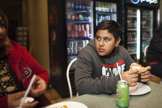 Thirteen-year-old Mike Mohammed chats with his mother, Jamela, over pizza.