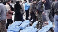 Free Syrian Army fighters and residents attempt to identify bodies found along a river, at a school used as a field hospital in Aleppo's Bustan al-Qasr January 29, 2013. At least 65 people, apparently shot in the head, were found dead with their hands bound in a district of the northern Syrian city of Aleppo on Tuesday, activists said. Opposition activists posted a video of a man filming at least 51 muddied male bodies alongside what they said was the Queiq River in the rebel-held Bustan al-Qasr neighbourhood of Aleppo. (Zain Karam/REUTERS)