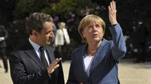 France's President Nicolas Sarkozy welcomes German Chancellor Angela Merkel as she arrives for a meeting at the Elysee Palace in Paris, August 16, 2011. (PHILIPPE WOJAZER/REUTERS)