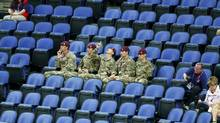 Soldiers sit in the empty seats held by the IOC as they watch the women's gymnastics qualification in the North Greenwich Arena during the London 2012 Olympic Games July 29, 2012. (MIKE BLAKE/REUTERS)