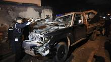 Police stand near a police car, which is destroyed after an explosion in front of a police station in Benghazi December 12, 2012. An explosive device planted near the car went off in front of the police station in Benghazi, injuring four policemen. (ESAM OMRAN AL-FETORI/REUTERS)