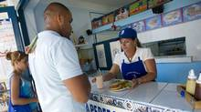 Cubans buy a meals t The Perfect Play in Havana. The restaurant has adopted a baseball theme that pays homage to the much-loved local team the Industriales. (Kevin Van Paassen/Kevin Van Paassen/The Globe and Mail)