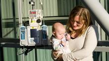The Hug is a lightweight wearable device for babies and small children that manages intravenous lines and other medical tubing. BCIT Research Analyst Sara Frederking, with baby Leila. (Scott McAlpine/BCIT)