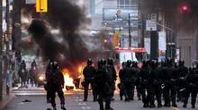 Riot police move towards a police car set on fire by anarchist demonstrators in the midst of protests on the streets during the G20 summit in Toronto. (MARK BLINCH/Mark Blinch/REUTERS)