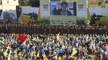 Supporters of Lebanon's Hezbollah leader Sayyed Hassan Nasrallah wave Hezbollah flags as they listen to him via a screen during a rally on the 7th anniversary of the end of Hezbollah's 2006 war with Israel, in Aita al-Shaab village in southern Lebanon, August 16, 2013. (ALI HASHISHO/REUTERS)