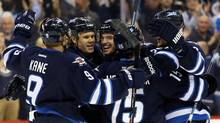 Winnipeg Jets defenseman Zach Redmond celebrates with teammates after scoring a goal against the Pittsburgh Penguins on April 3, 2014. (Bruce Fedyck/USA Today Sports)