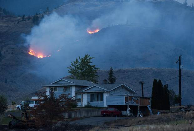 A wildfire burns on a mountain in the distance behind a house that remains standing on the Ashcroft First Nation, near Ashcroft, B.C., on Sunday July 9.