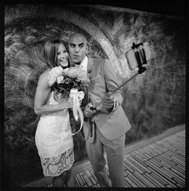 Jen Switzer and Tilak Kalaria pose with a selfie stick in front of an art installation at Toronto City Hall after getting married.