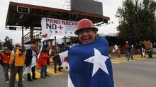 "A miner wrapped in a Chilean flag shouts slogans as he joins other strikers outside El Teniente copper mine near Rancagua city, about 100 kilometres south of Santiago, April 9, 2013. Workers said the one-day strike was a ""warning."" (IVAN ALVARADO/REUTERS)"