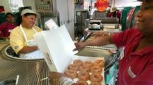 Maria Pereira, center, and Susan Jackson, right, load up a dozen glazed donuts for customers at the Krispy Kreme doughnut shop in the Dupont Circle neighborhood of Washington. (LAWRENCE JACKSON/AP/LAWRENCE JACKSON/AP)