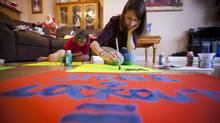 Highschool student Victoria Barker (L) and MacKenzie Timko paint signs that they will use during a student walk-out on Wednesday in Surrey, British Columbia on June 3, 2014. (Ben Nelms for The Globe & Mail)