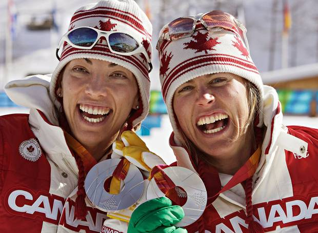 Beckie Scott (left) of Vermillion, Alberta, and Sara Renner of Canmore, Alberta show off their silver medals after winning them in women's team sprint cross-country skiing competition at the Olympic Games in Pragaleto Plan, Italy on February 14, 2006.