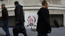 Pedestrians pass a portrait of former MF Global chief John Corzine across from the New York Stock Exchange. (MIKE SEGAR/REUTERS/MIKE SEGAR/REUTERS)