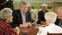 Canadian Prime Minister Stephen Harper plays cribbage with Verna Rutherford, left, Metha D'Amico and Ben Berg during a visit to the Trinity Lodge Seniors Home in Calgary, Alberta, December 23, 2012. (Mike Sturk/Reuters)