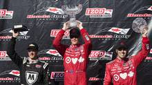 Winner Scott Dixon, centre, along with Sebastien Bourdais, left, and Dario Franchitti, right, celebrate at the Toronto Indy in Toronto on Saturday, 13, 2013. (CP)