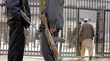 In this file photo dated Friday, Dec. 17, 2004, Afghan security police officers stand guard in front of the Pul-e Charkhi prison's gate in Kabul, Afghanistan. (MUSADEQ SADEQ/ASSOCIATED PRESS)